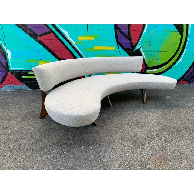 A Sleek floating curved sofa platform seat set on sculptural carved legs which blend seamlessly into the support for the...