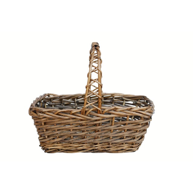 A traditional shopping or gathering basket made of woven wicker. An arch like handle is made with two wicker pieces woven...