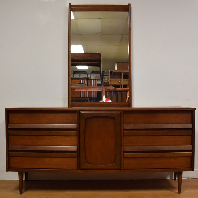 A mid-century modern walnut nine drawer dresser and mirror made of walnut by Bassett with a formica top and sculpted...