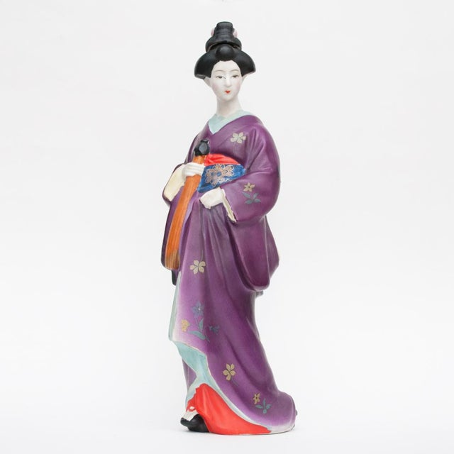A beautiful vintage Japanese bisque sake bottle in a shape of walking geisha, wearing kimono decorated with flowers. She...