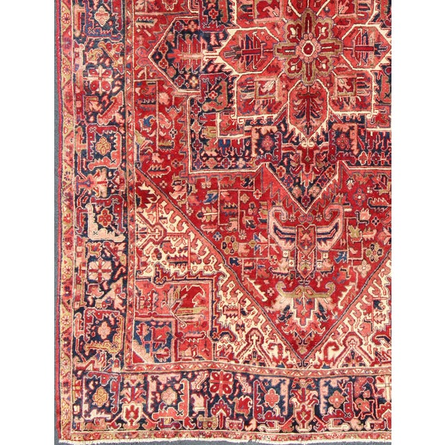 This magnificent antique Persian Heriz carpet from the mid-20th century bears an exquisite design rendered in gorgeous,...