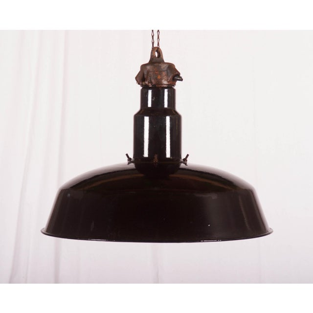 This pendant lamp was used in a factory in Czechoslovakia in the 1960s. It is made of a black enameled steel lampshade and...
