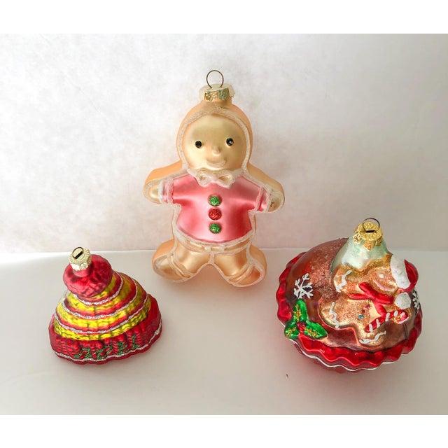 "Hand-painted blown glass Christmas tree ornaments. Hat measures 3""L x 2""D x 3.25""H; gingerbread man, 3.75""L x 2""D x 6""H."