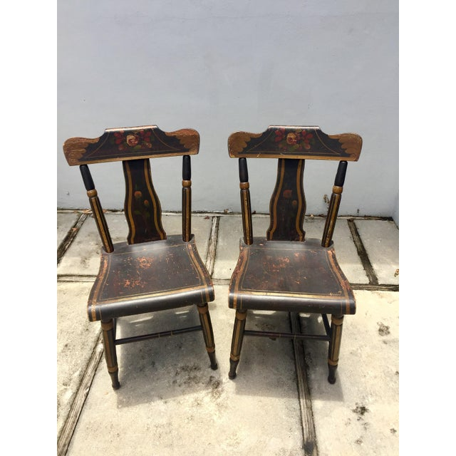 Pair of painted 19th Century chairs, Hitchcock Style. They are in original condition painted black with floral motif in...