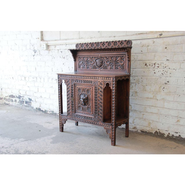 Offering a rare and stunning 19th Century ornately carved sideboard/bar cabinet. This piece features carved details...