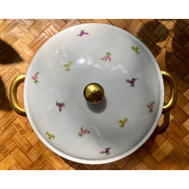 Rimmed in gold luster and delicately dotted with small pink, yellow and purple flowers with green leaves, this Johann...