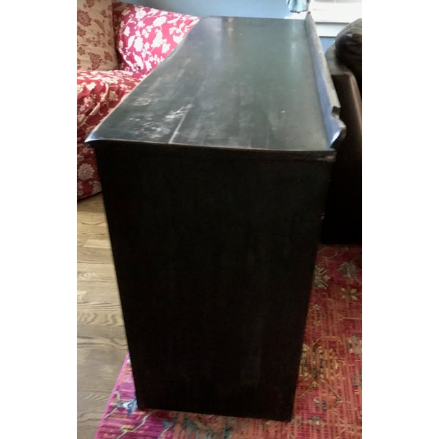 Dark wood. Handles are a pirate theme but can be changed. Three center drawers, one pull out table. Two size doors with...