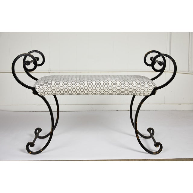Late 20th century Hollywood Regency style iron bench with elegant scrolling arms and legs supporting an upholstered seat...