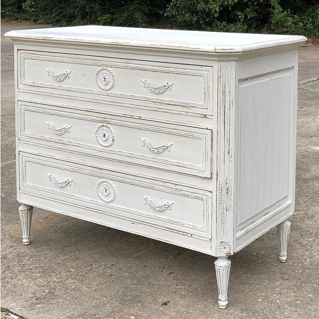 19th Century Country French Louis XVI Painted Commode features subtle hand-carved embellishment enhanced by the patinaed...