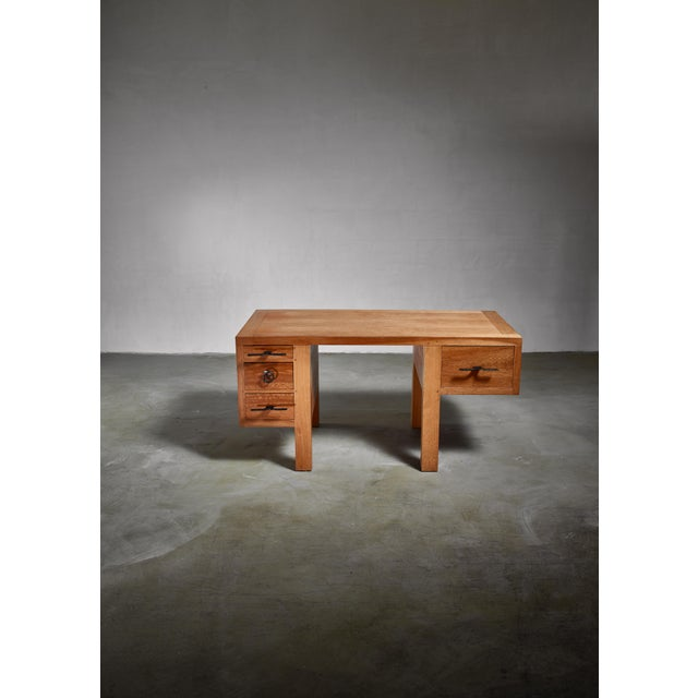 A solid oak desk by Jean Touret for Atelier Marolles. The desk has four drawers with sculptural wrought iron handles. The...