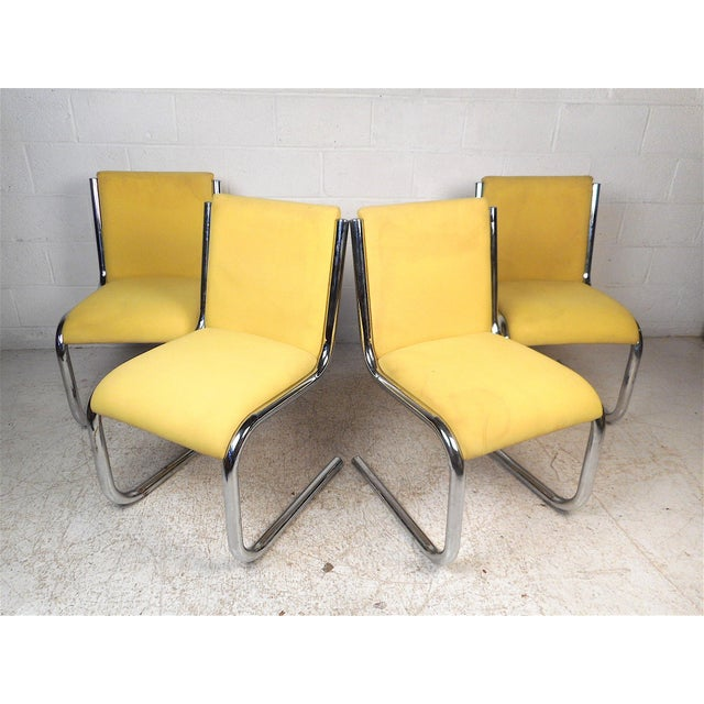 Stylish set of 4 midcentury chrome cantilevered chairs with vibrant yellow vintage upholstery. This set is sure to be a...