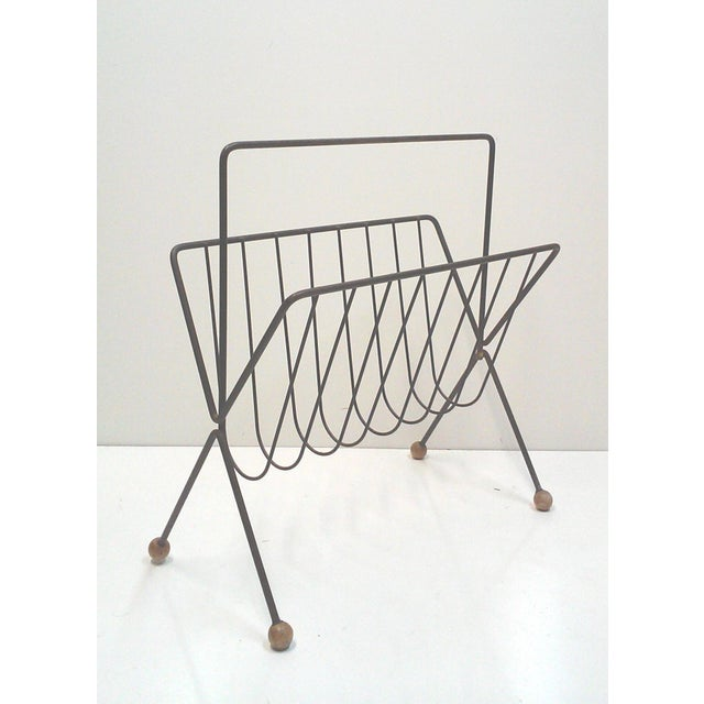 "Tony Paul magazine rack in black iron with wooden ball feet and an ""X"" style profile. This Mid-Century rack designed by a..."