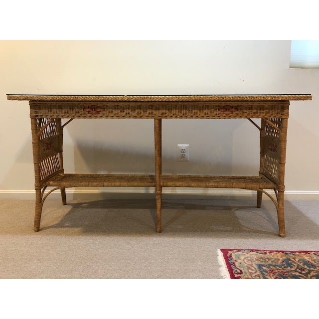 This is a vintage painted wicker console table with a glass top. The piece dates back to the 1950s. Light brown paint with...