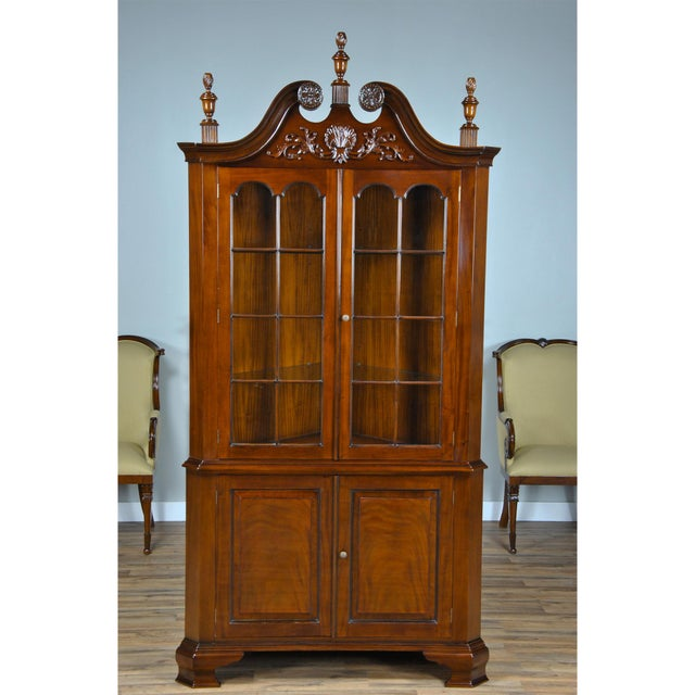 The Carved Corner Cabinet from Niagara Furniture is an oversize two piece corner cabinet with carving on the swan neck...