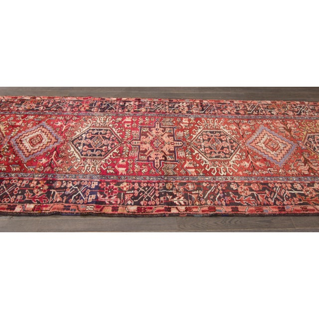 Vintage hand-knotted Heriz with a geometric design on a red field. This rug has magnificent detailing and would be perfect...