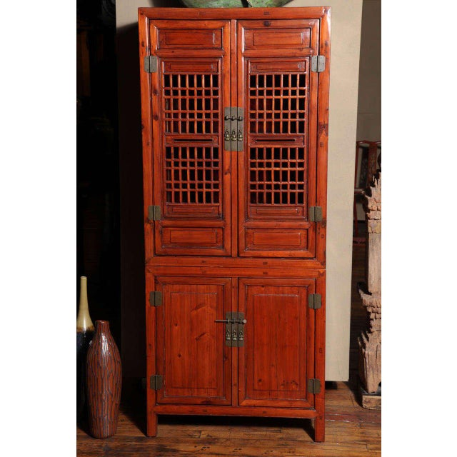 A tall Chinese cabinet with fretwork doors from the 19th century. This Chinese tall kitchen cabinet features four doors...
