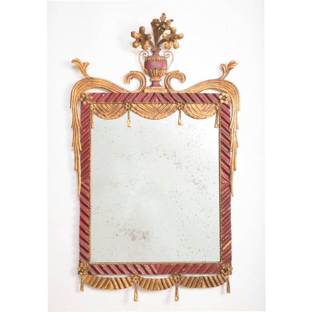 Italian Rococo style painted tole mirror, the 'Venetian Red' ribbon frame with gilt faux drapery swags topped by an urn...