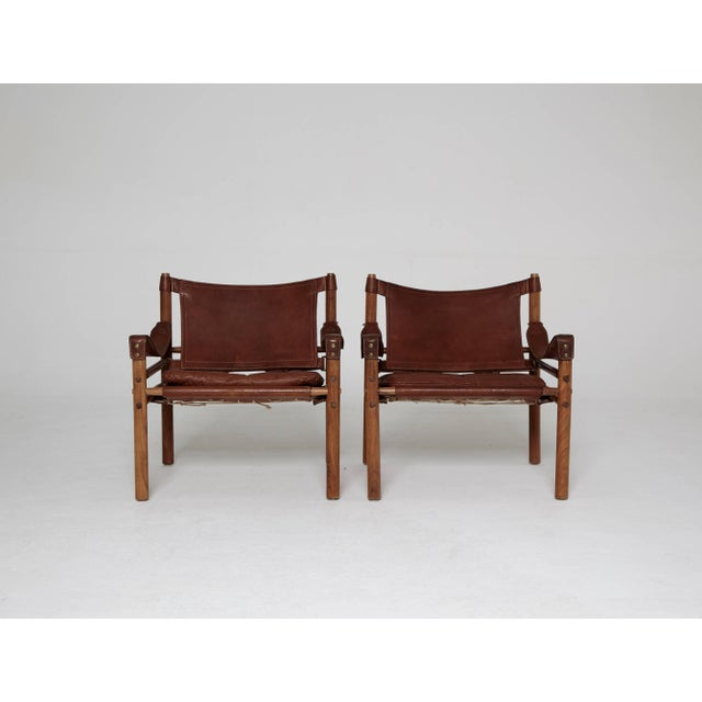 A stunning pair of authentic vintage Arne Norell safari sirocco chair in rosewood and brown leather. Made by Norell Mobler...