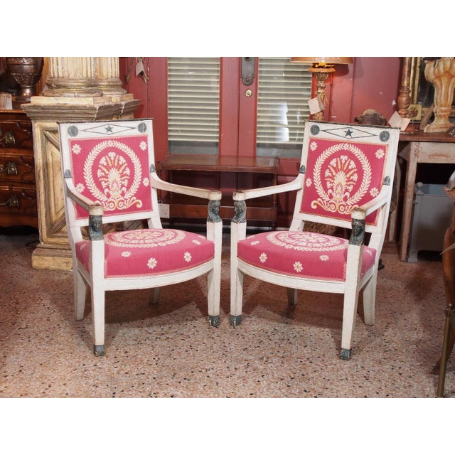 A pair of Consulate painted fauteuils. Straight back with star inside a diamond flanked by rosettes. Empire painted heads...
