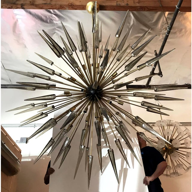 Italian Sputnik chandelier shown in smoky Murano glass shards with black enameled centre on natural brass frame designed...