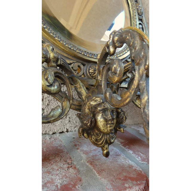 Antique french brass wall sconce light fixture with oval mirror art nouveau directly from France. Ornately embellished in...
