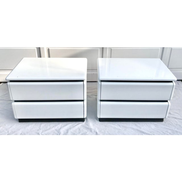 Here is a great Pair of rare 1980's nightstands by Roger Rougier. They are white lacquered, laminate nightstands with...