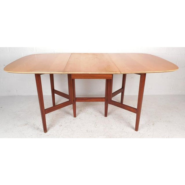 Stunning Mid-Century Modern drop-leaf dining table features solid walnut tapered legs and a vintage maple finished top....