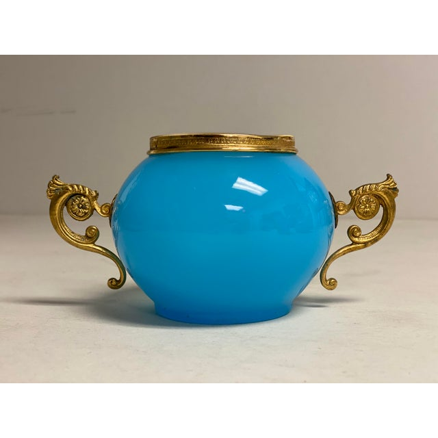 A 19th century blue opaline round cachet pot or vase from France with gilt flowers and scroll handles.