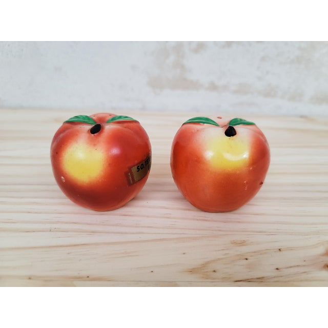 """Kitschy mid-century salt and pepper set shaped as peaches. One is labeled """"So. Texas State Fair Beaumont"""". Each measures..."""
