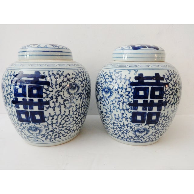 A pair of blue and white covered ginger jars. The flat surface of the lid and the vases are ornamented with double Chinese...