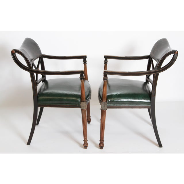A pair of stylish Regency black and gilt chinoiserie lacquered armchairs with curved open arms. The back consists of a...