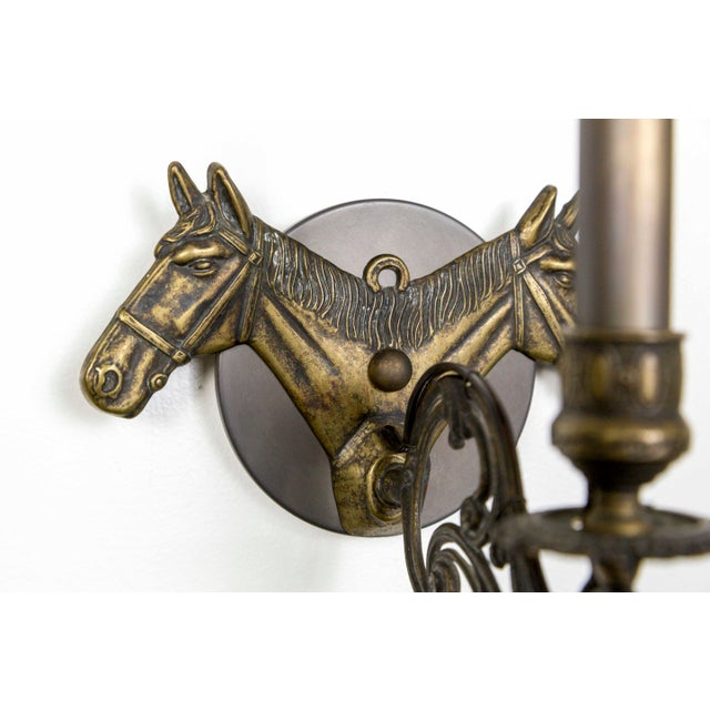 A refined pair of all brass candelabra sconces with a design of double profile of horse heads in low relief. A unique...
