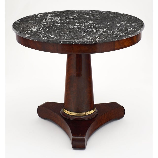 """A sleek French Empire period """"gueridon"""" with gray marble top. The base is made of Cuban flamed Mahogany with a tripod..."""