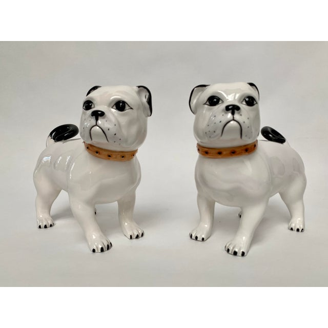 Pair of large white ceramic pug figurines made in Italy, ca. 1950s. The all-white dogs feature black ears and tails, brown...