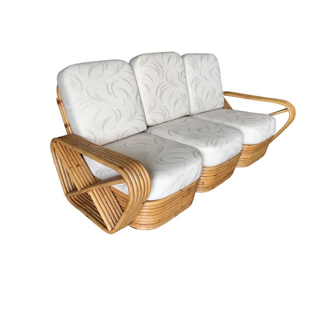 Paul Frankl style rattan living room set including a matching three-seat sectional sofa, and pair of end tables. The sofa...
