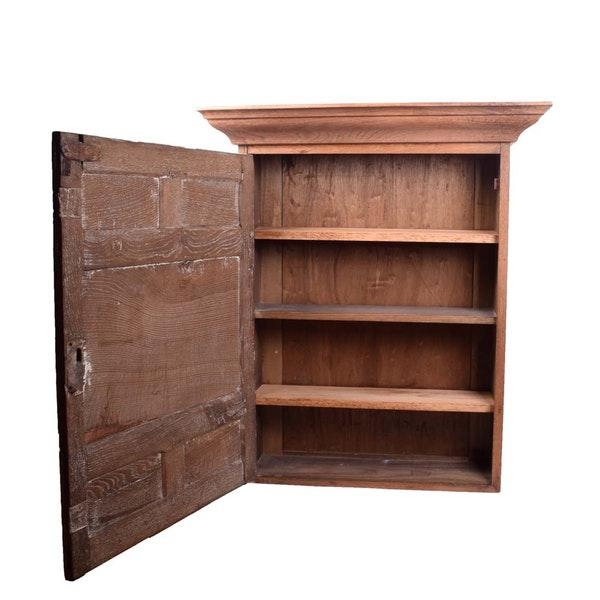 A vintage wall rustic or farmhouse mountable cabinet. The wooden cabinet features crown molding to the top with a single...