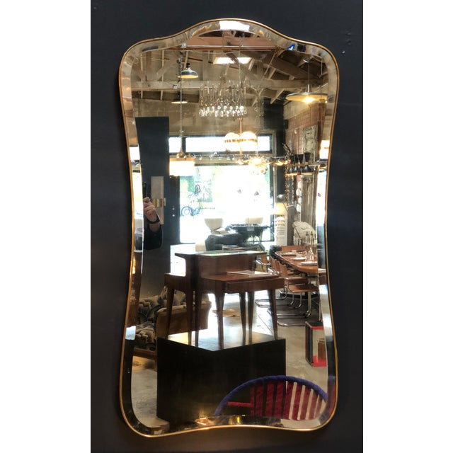 An eclectic vintage brass mirror, Italy midcentury. The long brass frame has a distinctly linear and corrugated shape.