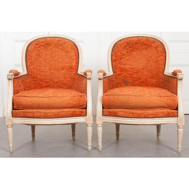 A pair of painted and upholstered French 19th century Louis XVI style bergères. The chairs date to the 1870s, when they...