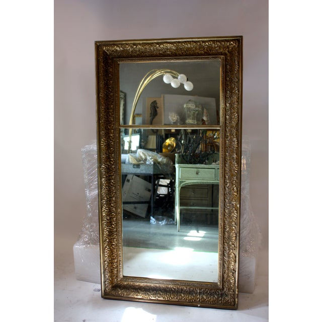 This is an antique floor mirror that's beautifully carved with nice patina. The piece dates back to the late 18th century.