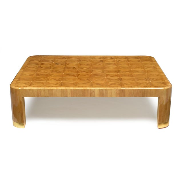 A spectacular cocktail table inspired by Jean Michel Frank with a dazzling patterned marquetry top, radius legs and gold...