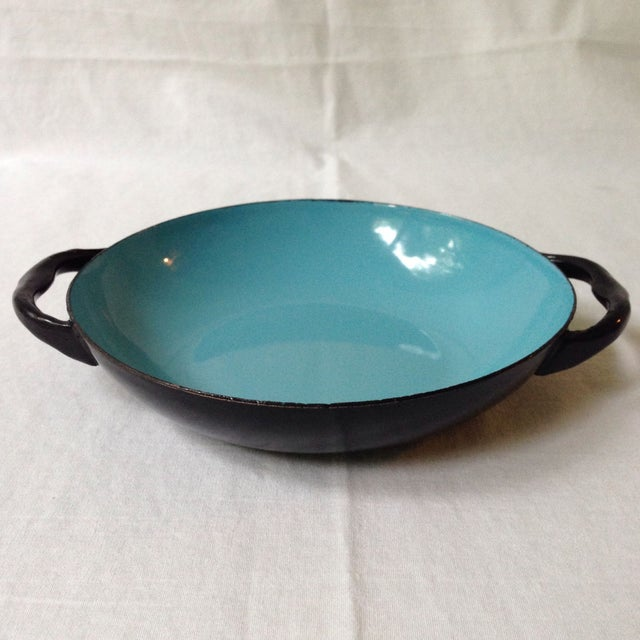 Vibrant handled bowl with a glossy black exterior and blue enameled interior. A perfect decorative item for the kitchen....