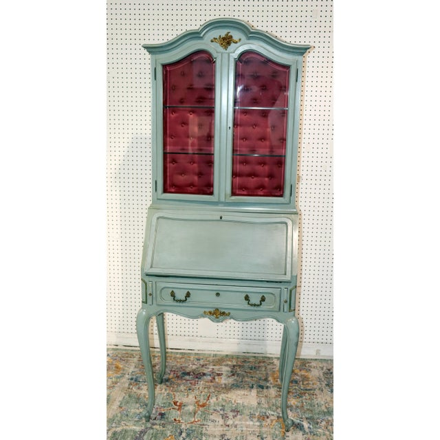 French Louis XV style secretary desk with bronze hardware. The top has 2 doors with 2 glass shelves and a silk tufted...