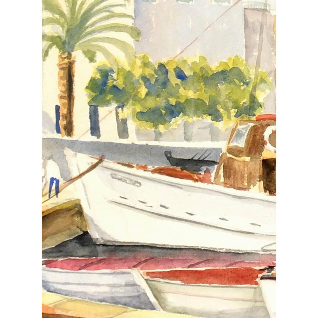 Watercolor painting of boats docked along a scenic Mediterranean coast lit by golden sunlight, circa 1960. Displayed on a...