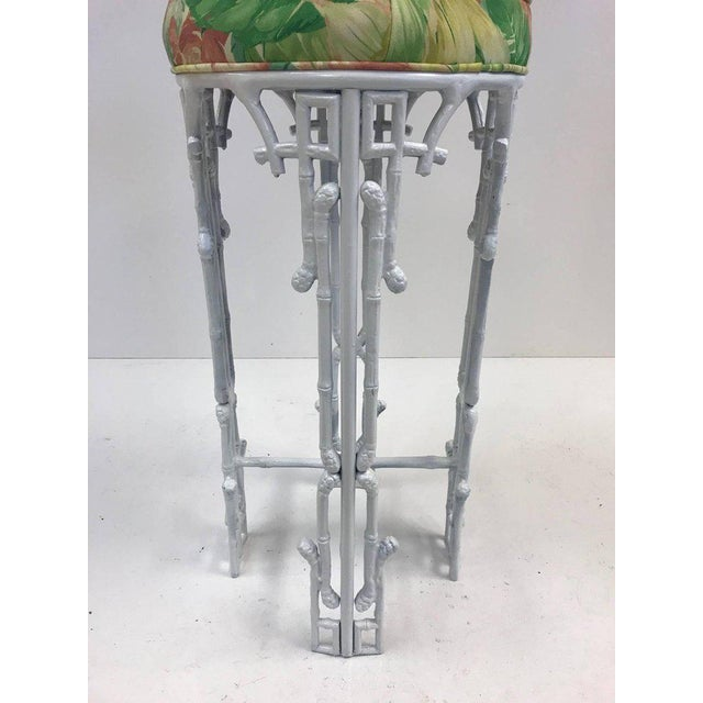 Three, cast iron, faux bamboo bar stools. Has a white painted frame with original tropical upholstery.