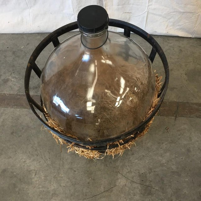 Rustic antique carboy demijohn with iron basket holder. This piece is a handsome glass wine holder bottle, cushioned with...