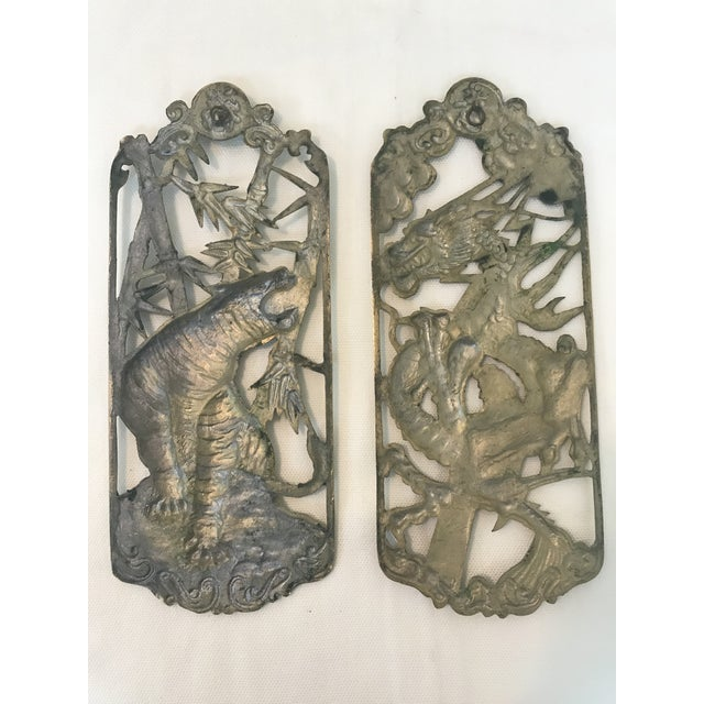 Two brasstone cast metal wall plaques featuring chinoiserie motifs. One plaque features a tiger with bamboo and one...