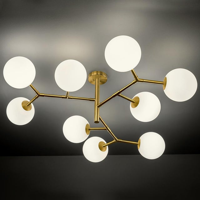 Brushed brass constellation light consisting of 9 arms with opal globes. The glass globes have a threaded insert to screw...