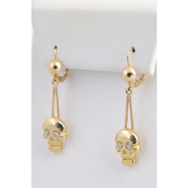 Dangling skull 14K yellow gold pierced earrings with diamond eyes (.08c atw.). H 1.3 in. x length .4 in. depth dimensions...