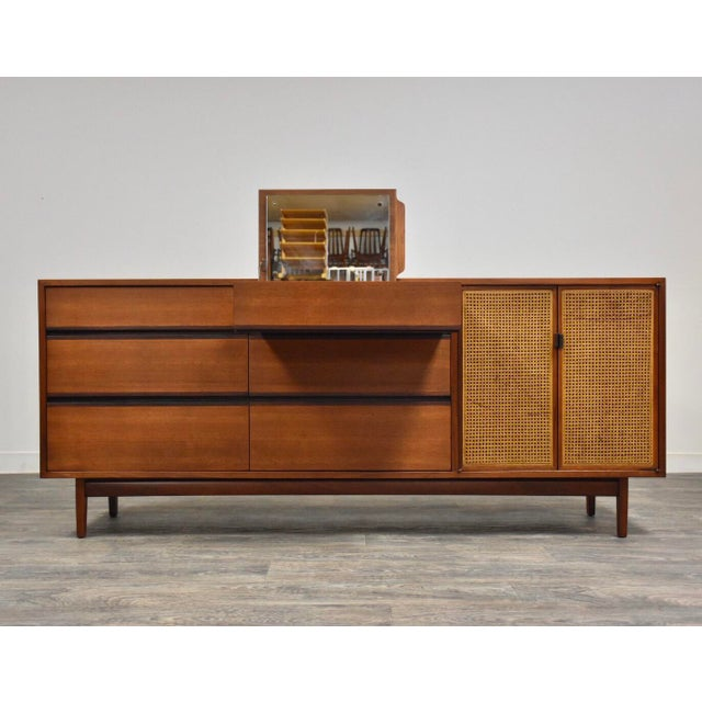 A beautiful mid century modern walnut dresser or credenza with rosewood colored accents and cane doors that open up to...