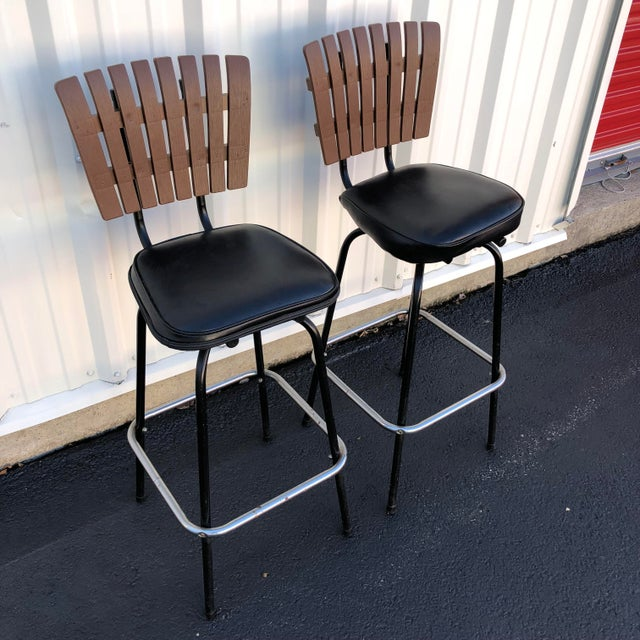 This pair of mid century bar stools feature vintage black vinyl upholstery, swivel seats, and unique leg design offering a...